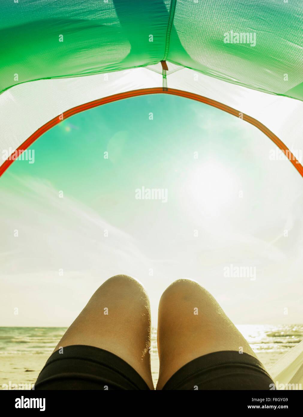 Legs in camping tent door on beach - Stock Image