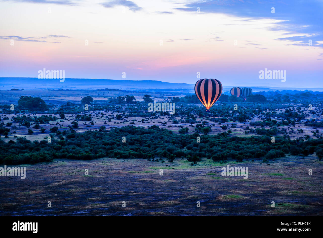 Hot air balloon flying over savanna landscape - Stock Image