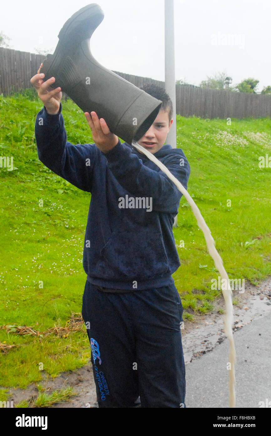Boy pours water out of welly in Alford in Aberdeenshire, Scotland. Stock Photo