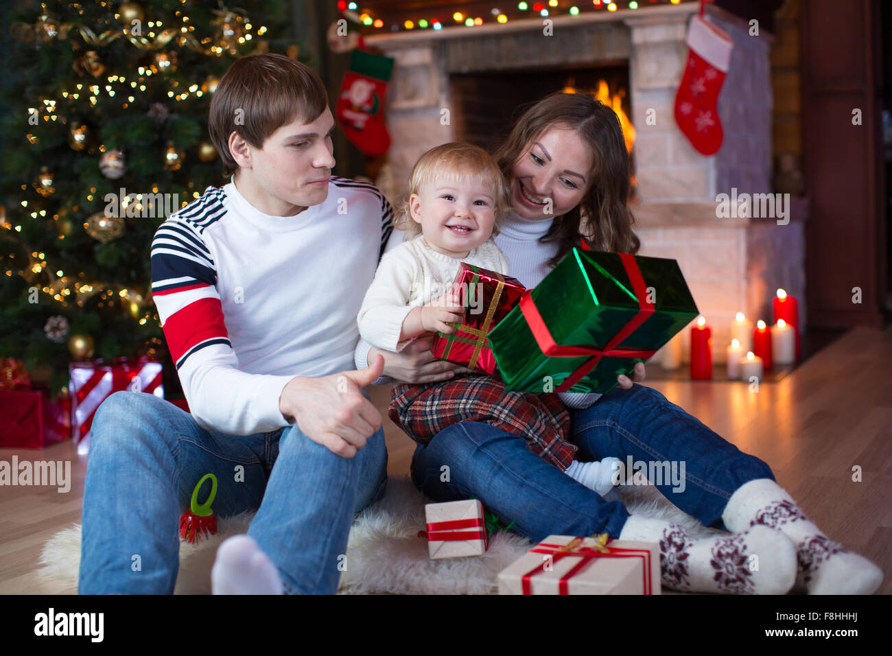 Happy family - father, mother and little son sitting with gifts near ...