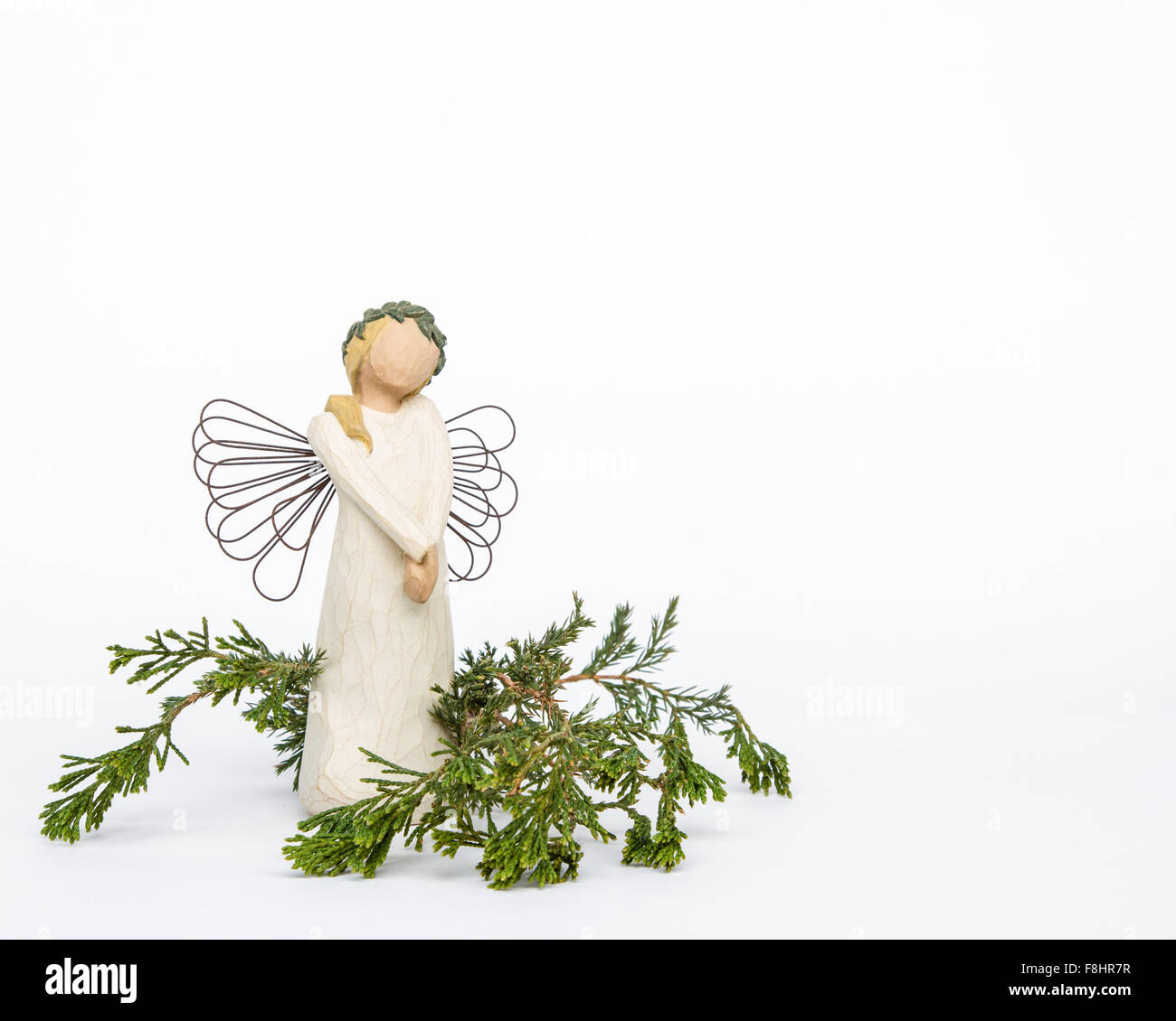 Faceless angel ornament with metal wings in a bed of live evergreens on white background with negative space on - Stock Image