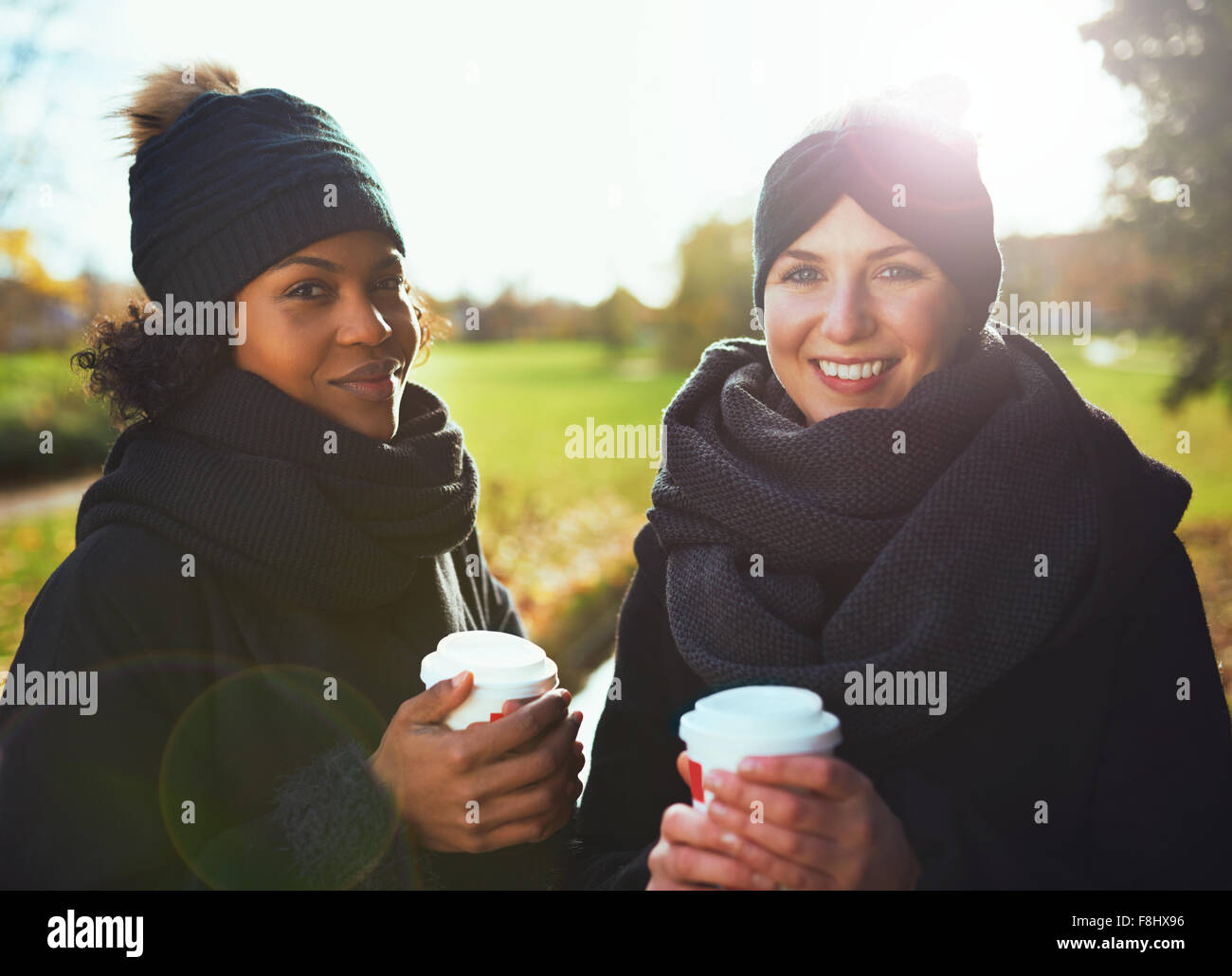 Two young women looking at camera, smiling while holding coffee to go against of autumnal park - Stock Image