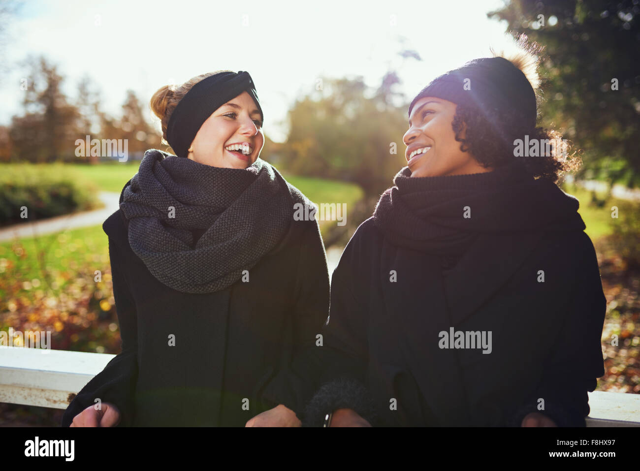 Two women in warm clothes standing on bridge in park and smiling at each other - Stock Image