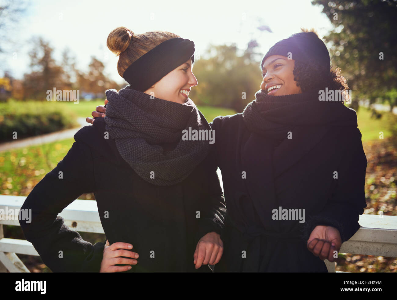Two girlfriends looking at each other and smiling,standing on the bridge in park - Stock Image