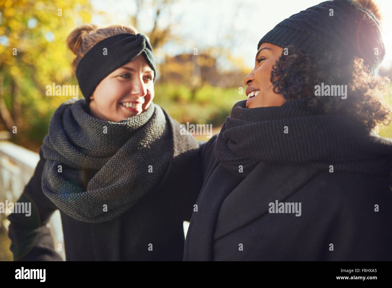 Two girlfriends looking at each other and smiling while standing in autumnal park - Stock Image