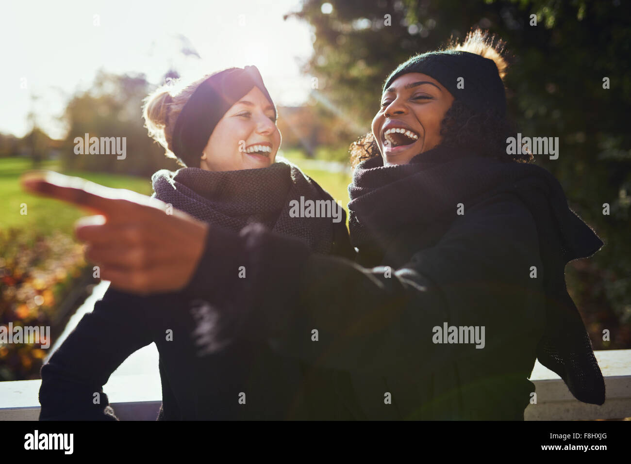 Two women laughing at something while standing in park - Stock Image