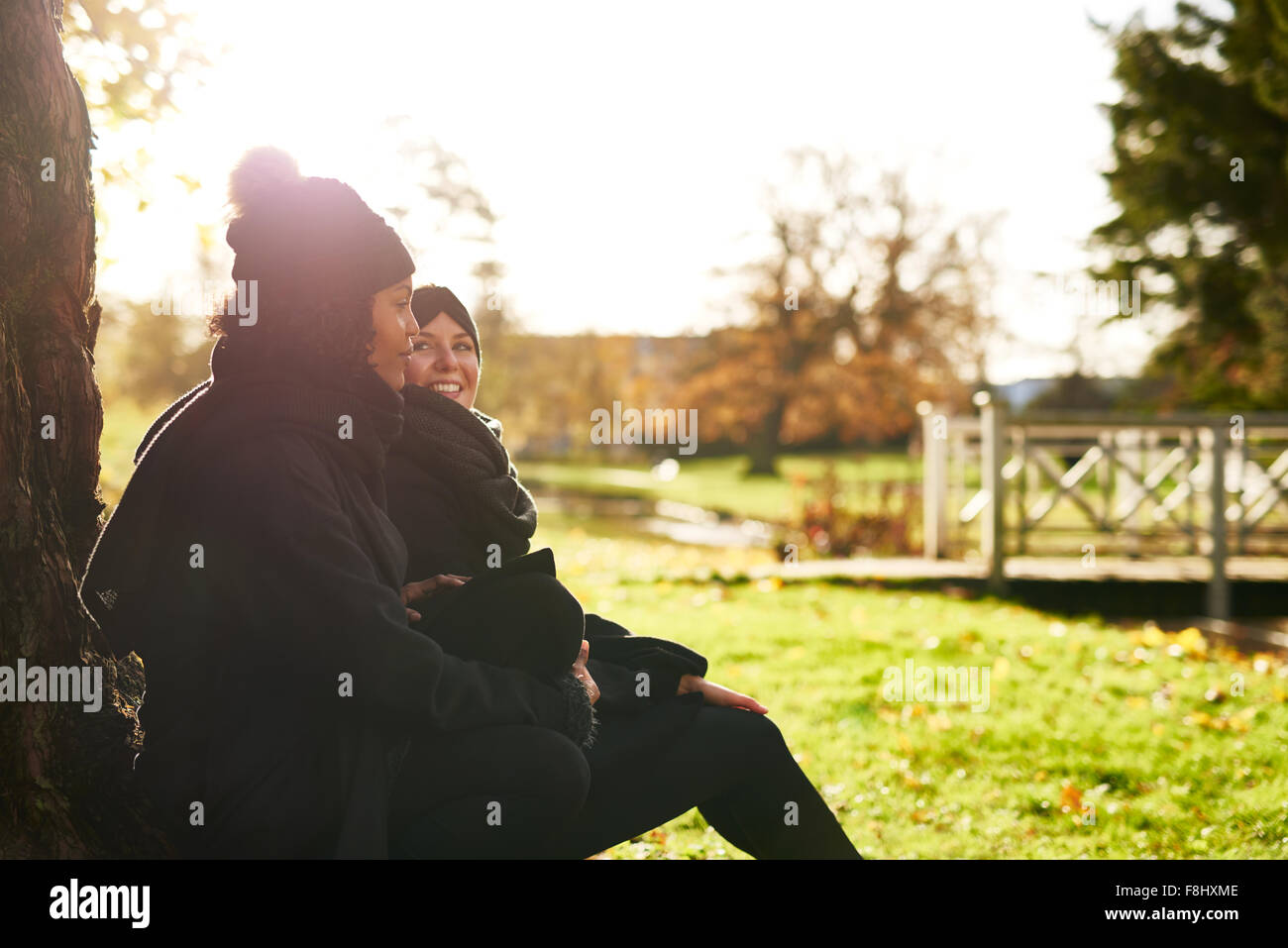 Two young women sitting in autumnal park, leaning on tree trunk.Sunny - Stock Image