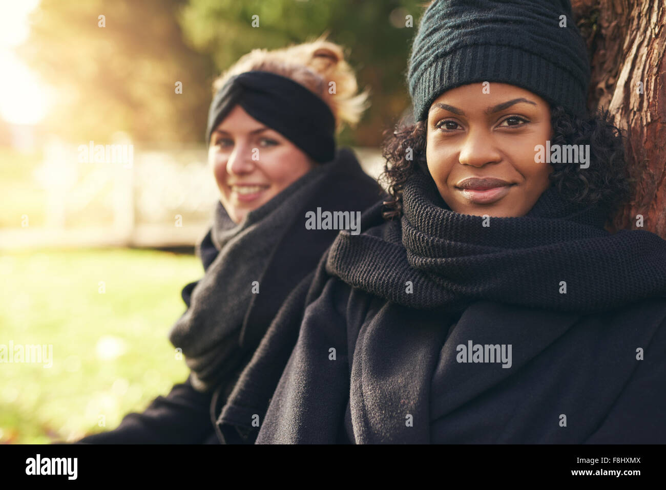 Close-up of two smiling young women leaning on tree trunk in autumnal park - Stock Image