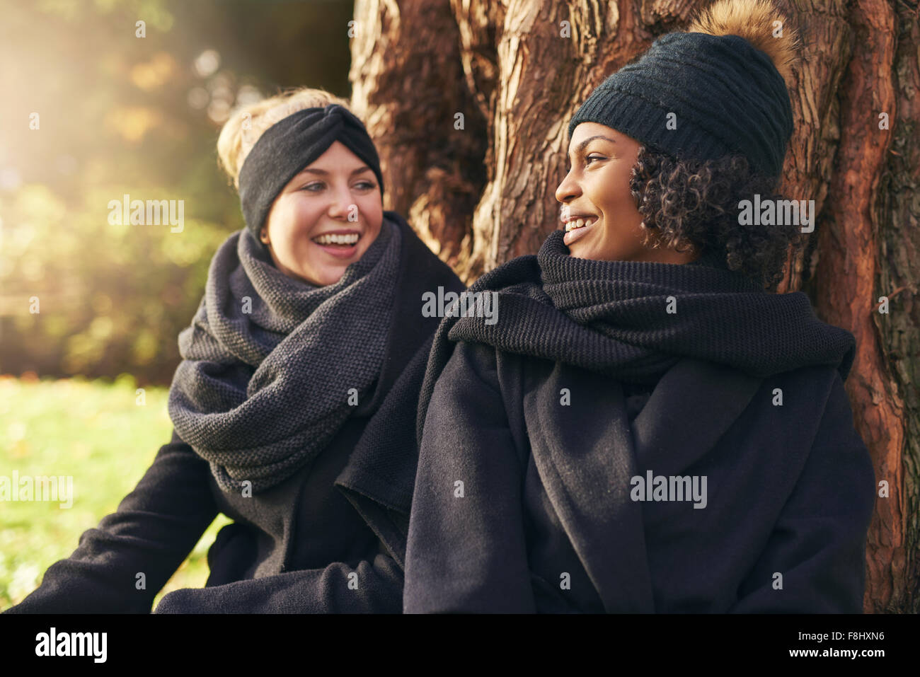 Close-up of two smiling young women leaning on tree trunk in autumnal park and looking at each other - Stock Image