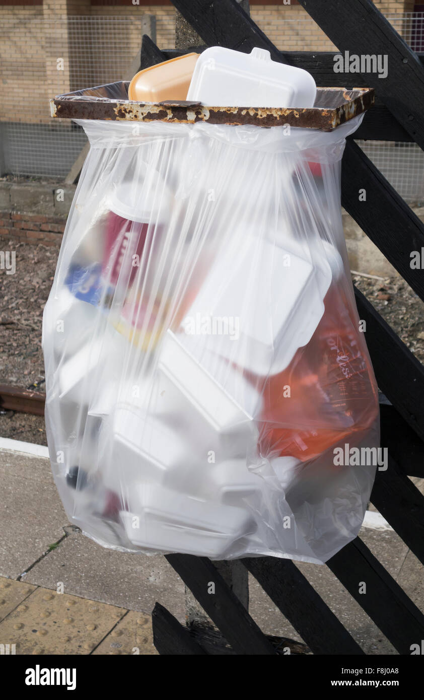 Plastic litter bin full of styrofoam takeaway food trays on railway station platform. England, UK - Stock Image