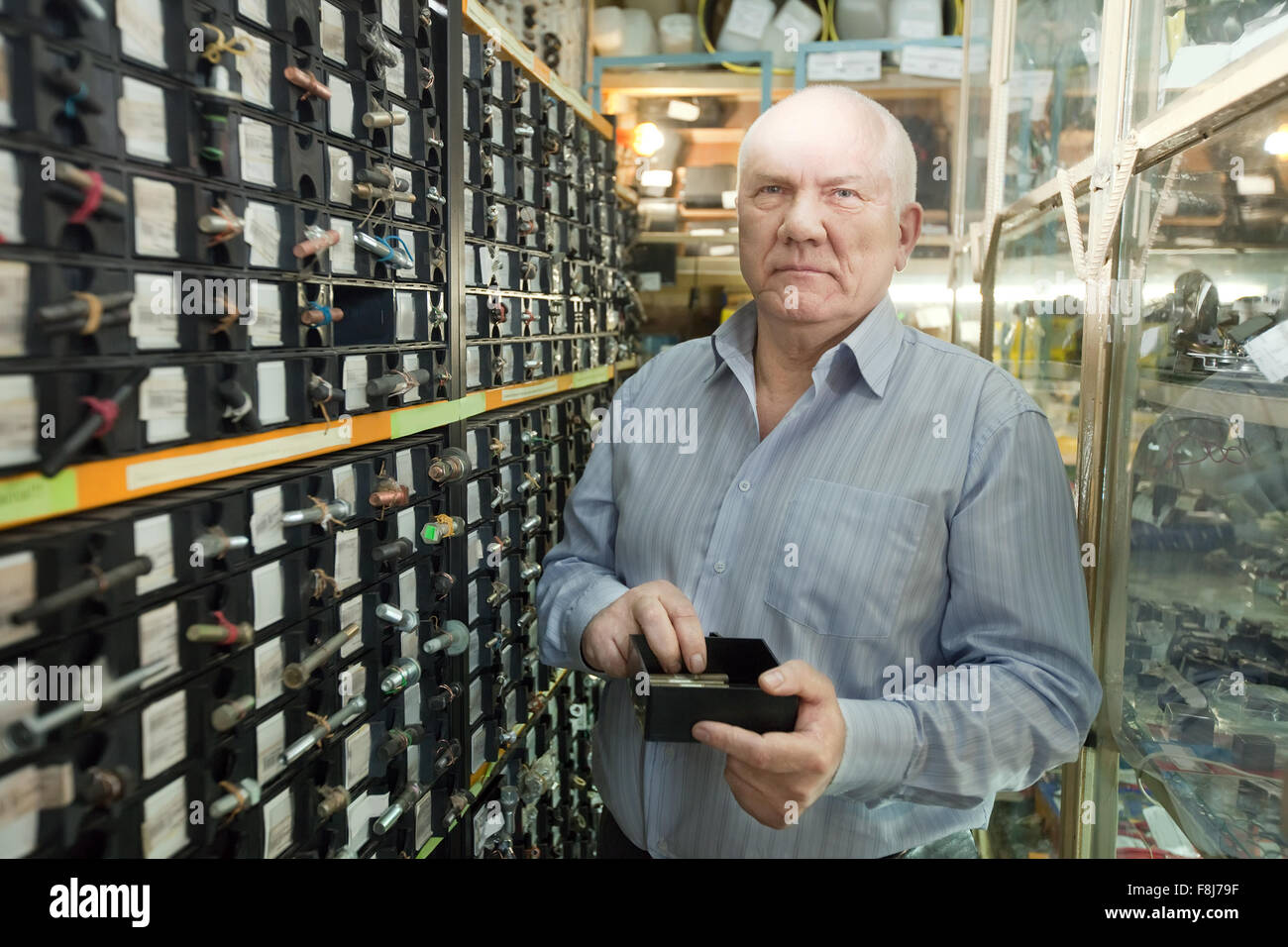 mature man chooses fasteners in  auto parts store - Stock Image