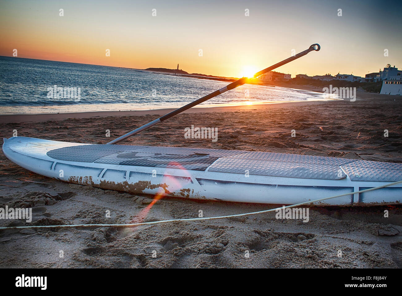 Paddle board on the sand at sunset. - Stock Image
