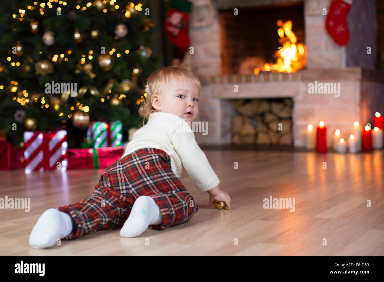 kid crawling to gifts lying under Christmas tree Stock Photo ...