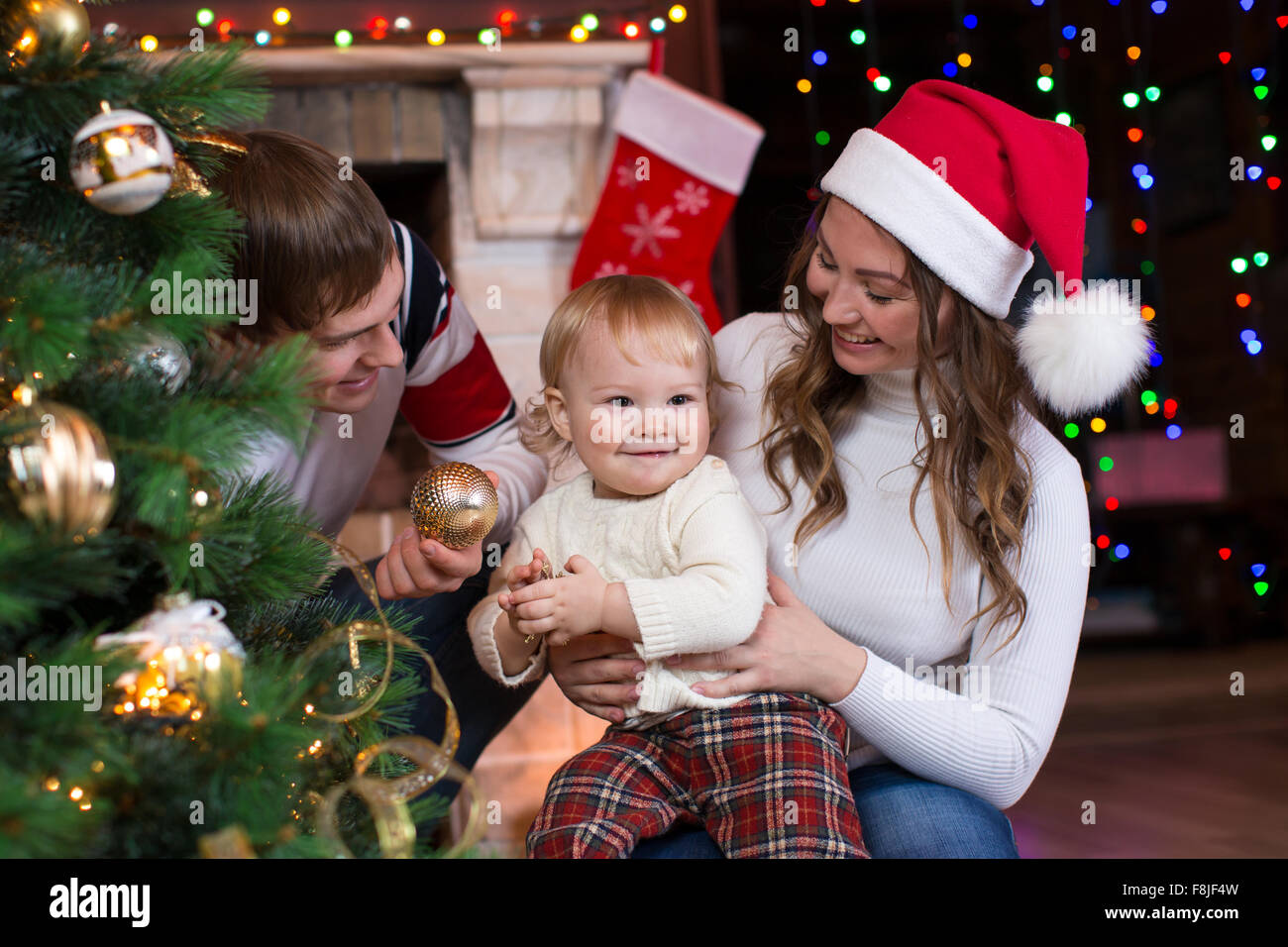 Happy family with child decorating Christmas tree in front of fireplace  in living room - Stock Image