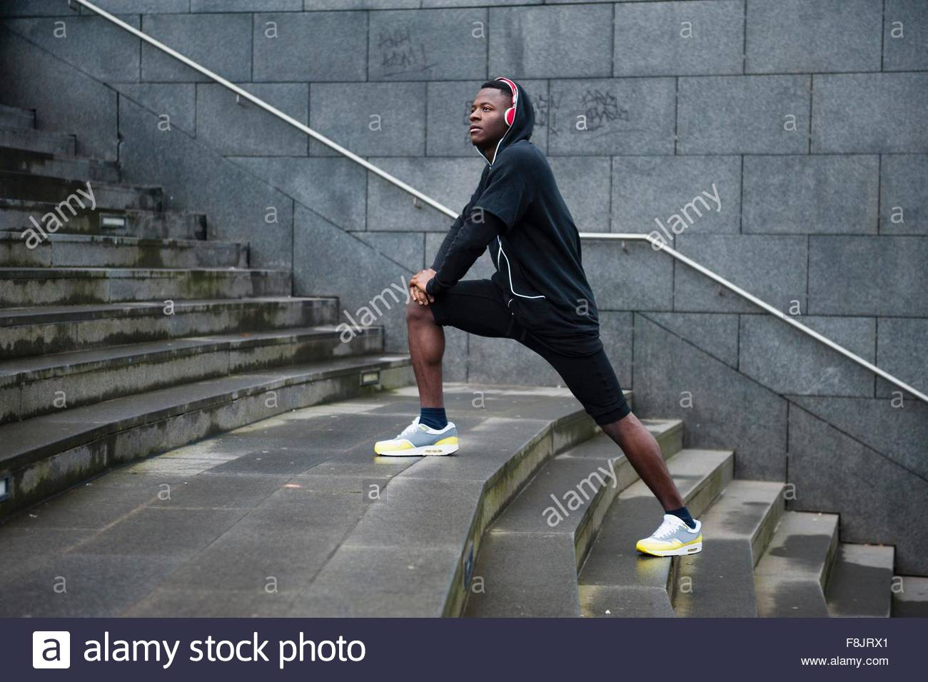 Young man exercising, stretching legs on steps, outdoors Stock Photo