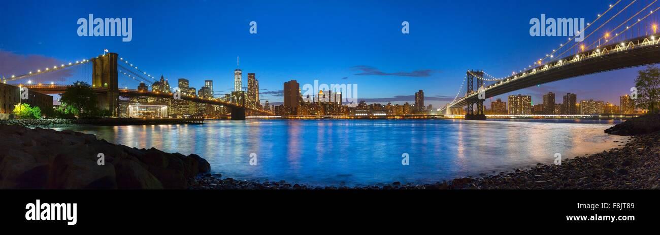 Panoramic view of Manhattan and Brooklyn bridges at night, New York, USA - Stock Image
