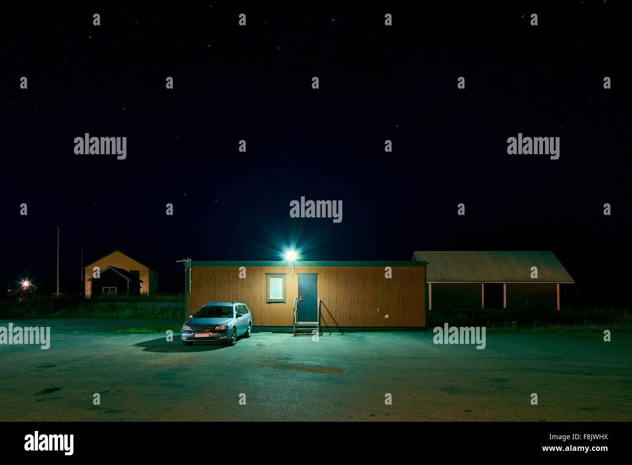 Car parked outside spotlit hut at night, Kalmar, Sweden - Stock Image