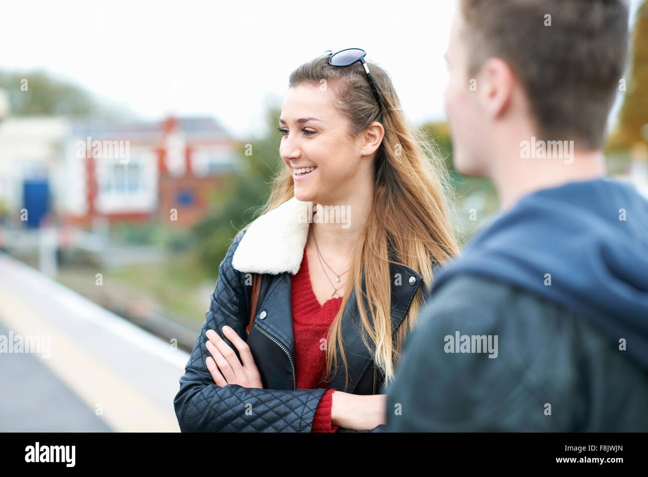 Young woman  and young man standing on railway platform - Stock Image