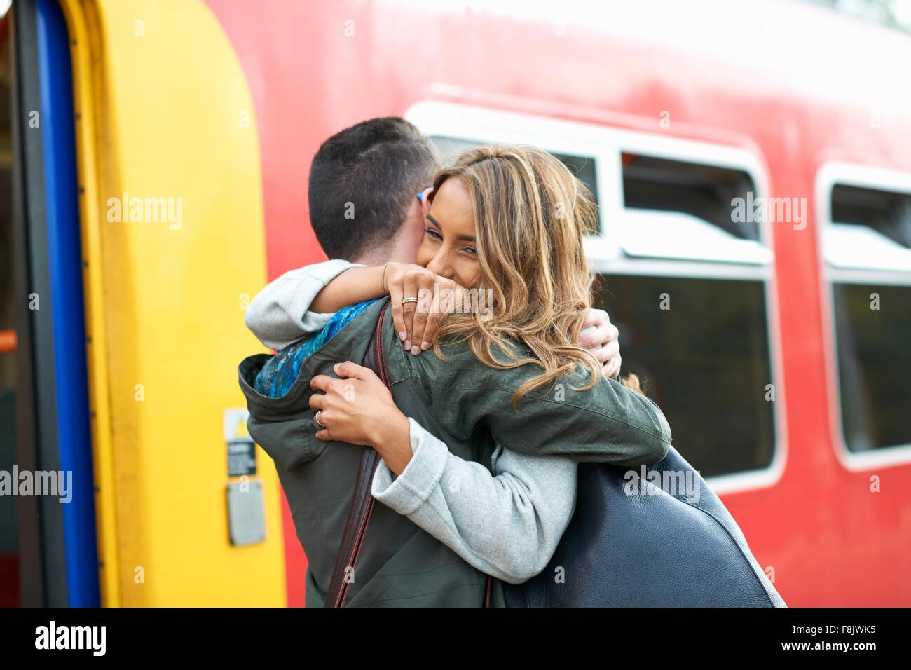 Heterosexual couple hugging at railway station - Stock Image