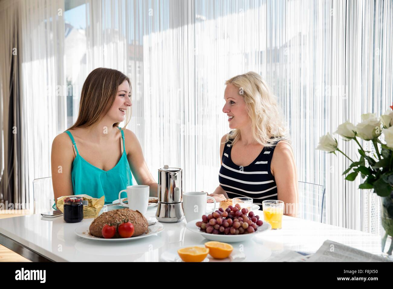 Women sitting at dining table enjoying a continental breakfast together, face to face smiling - Stock Image