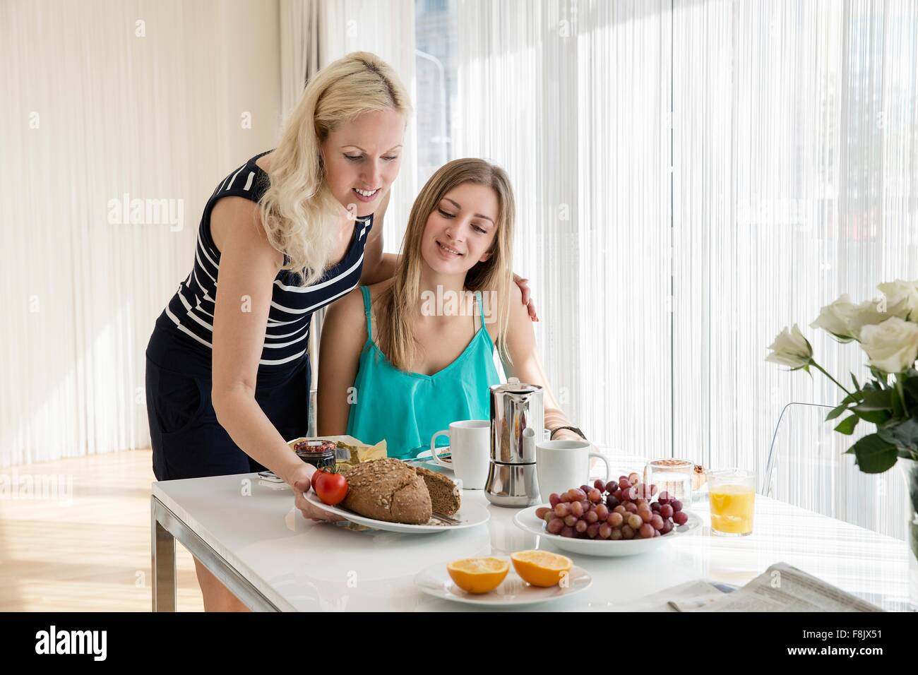 Woman serving friend continental breakfast - Stock Image
