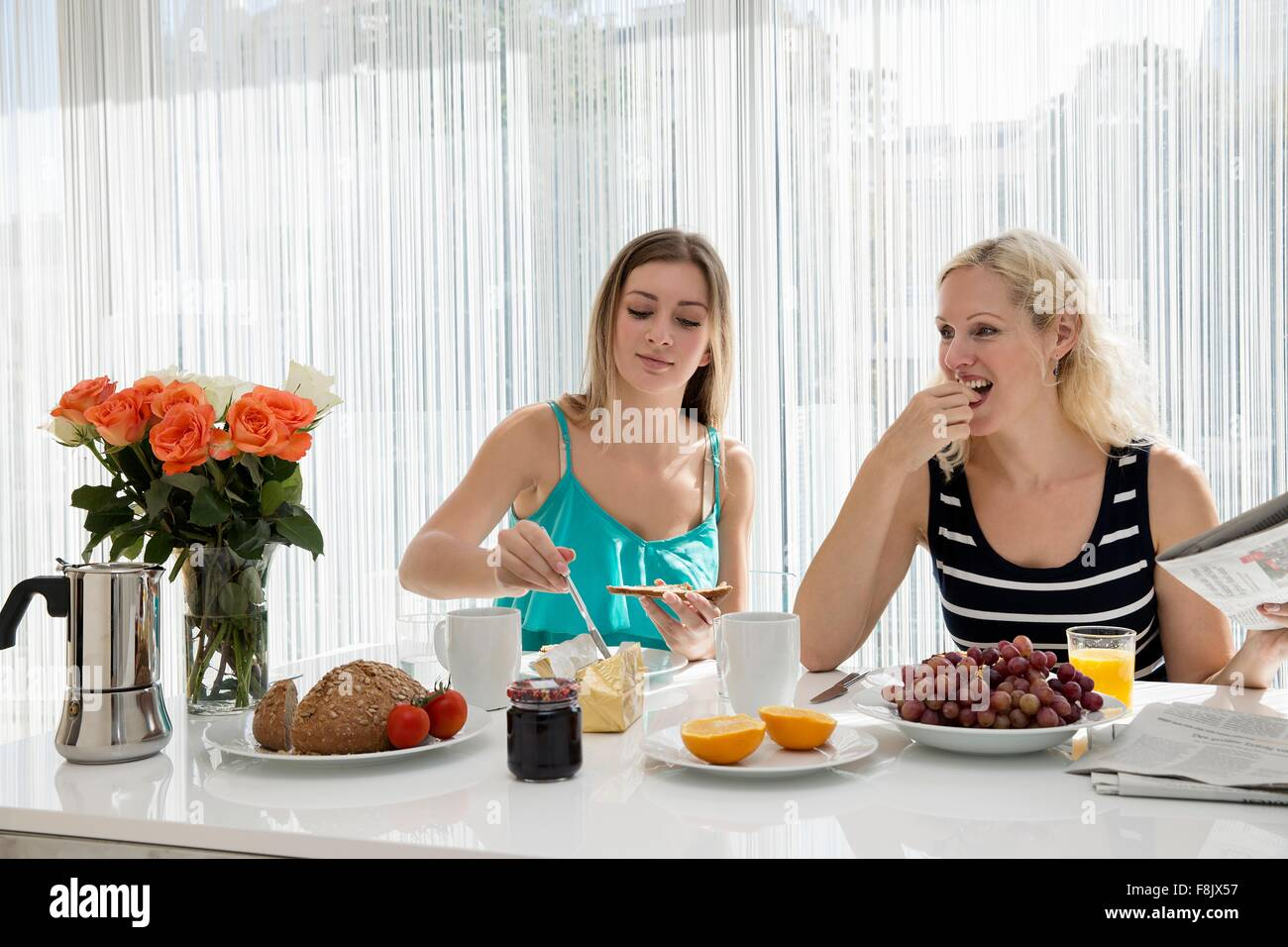 Women sitting at dining table spreading butter on bread, eating a continental breakfast together - Stock Image