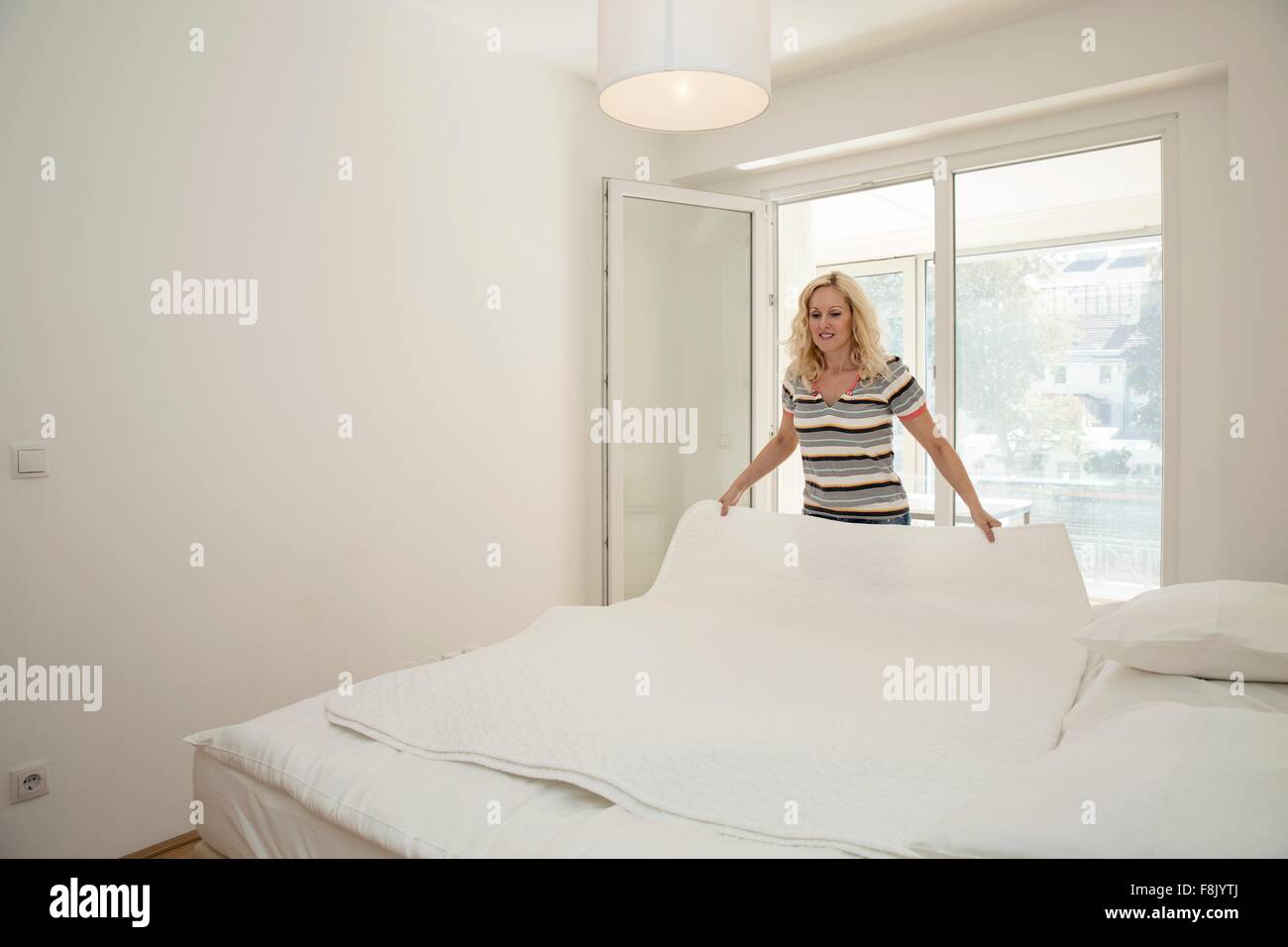 Mature woman in bedroom holding blanket making bed - Stock Image