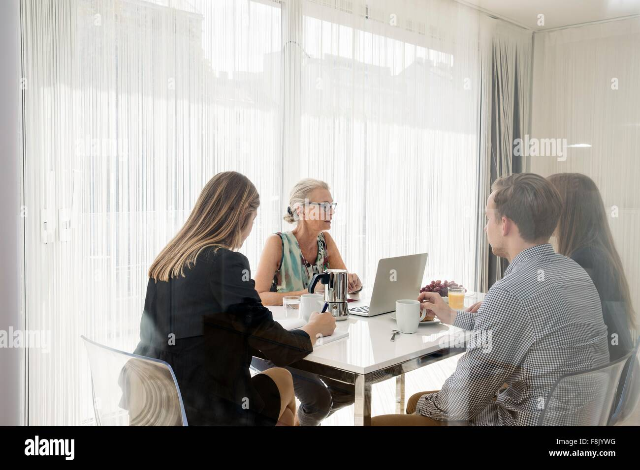 View through window of colleagues sitting at table having business breakfast meeting - Stock Image