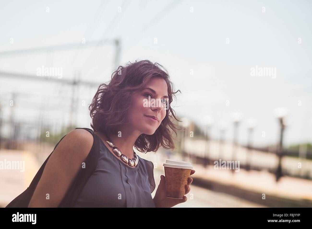 Mid adult woman waiting at train station, holding coffee cup - Stock Image