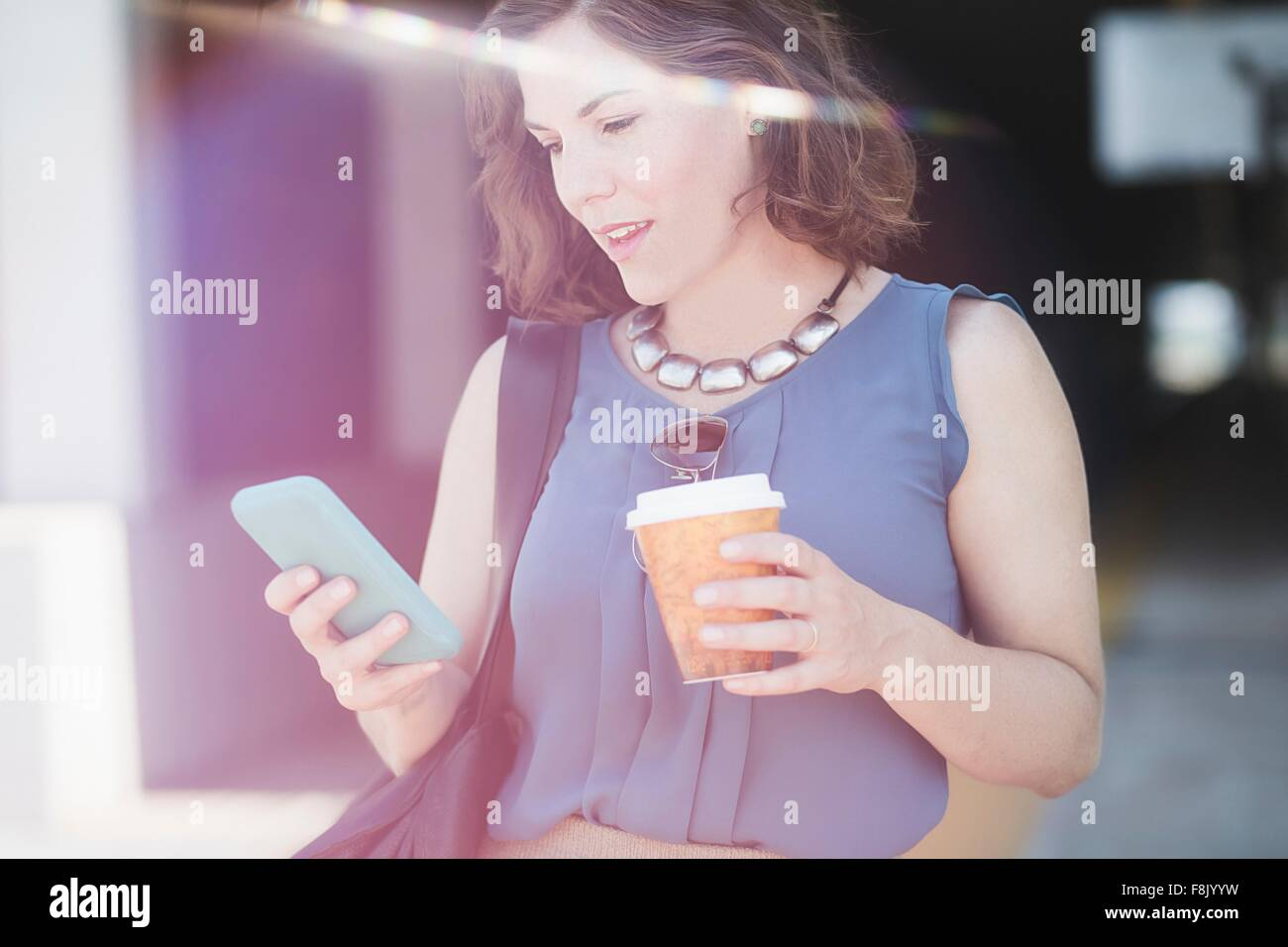 Mid adult woman outdoors, using smartphone, holding coffee cup - Stock Image