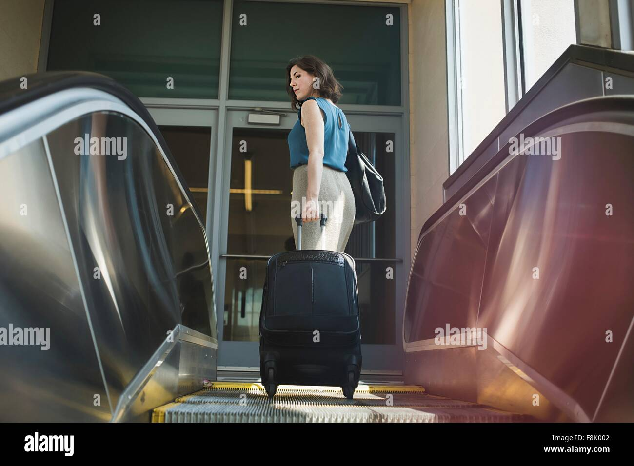 Mid adult woman using escalator, holding wheeled suitcase, rear view - Stock Image