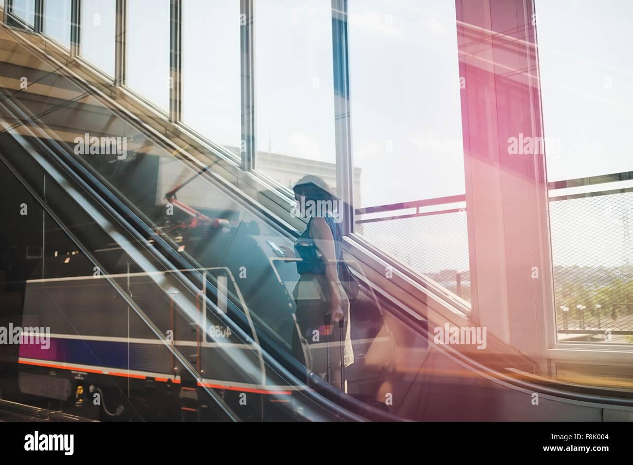 Mid adult woman using escalator, holding wheeled suitcase and smartphone - Stock Image