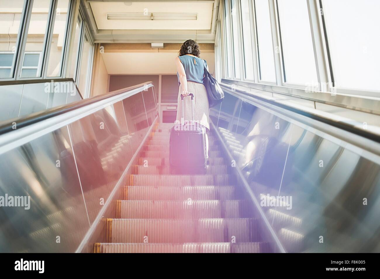 Mid adult woman using escalator, holding wheeled suitcase, rear view, low angle view - Stock Image