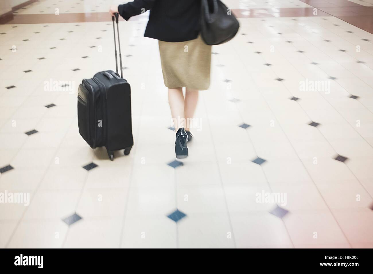 Mid adult woman walking with wheeled suitcase, rear view, low section - Stock Image