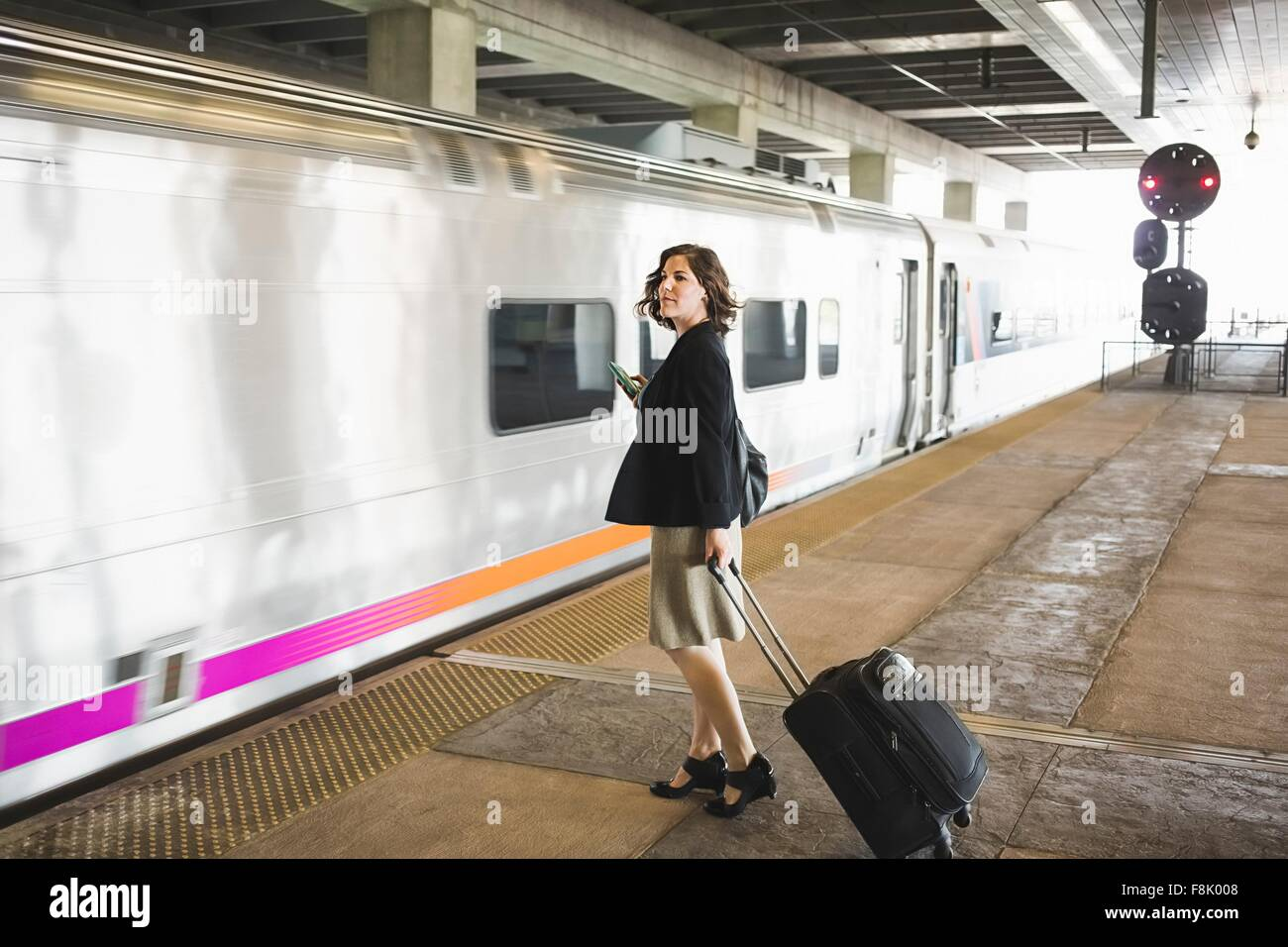 Mid adult woman waiting to board train, holding wheeled suitcase and smartphone - Stock Image