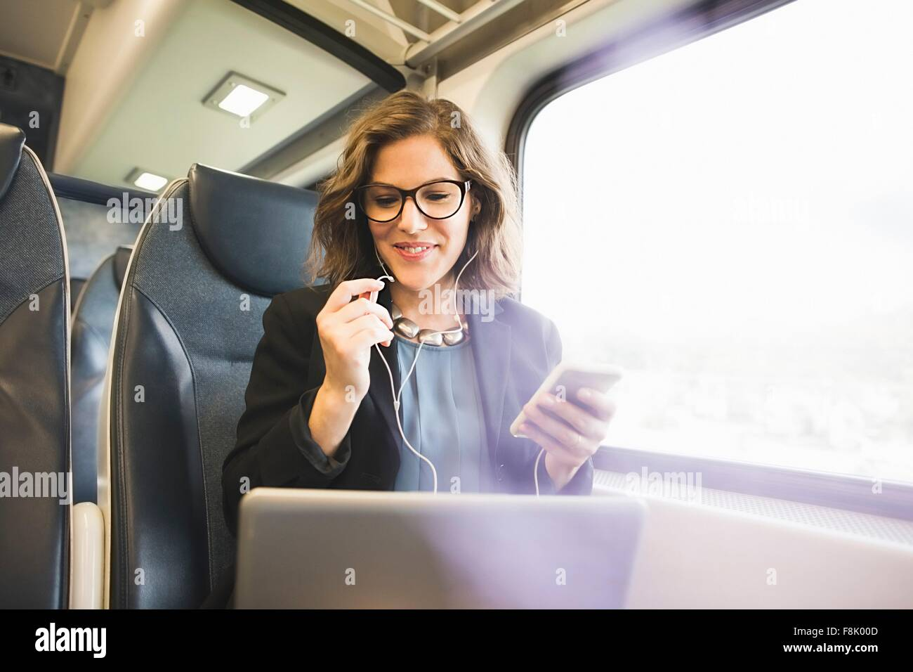 Mid adult woman on train, holding smartphone, looking at laptop - Stock Image