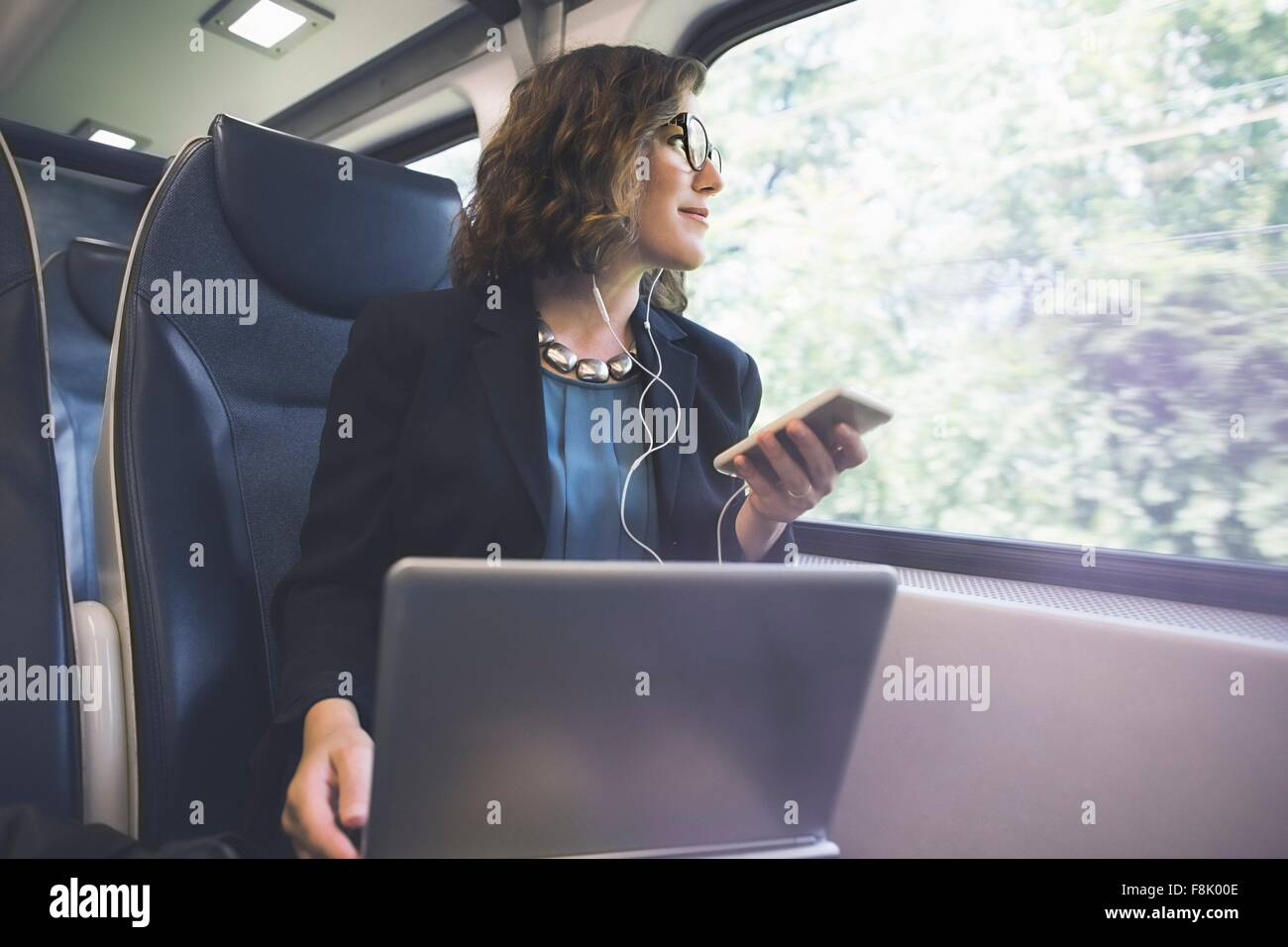 Mid adult woman on train, holding smartphone, laptop in front of her - Stock Image
