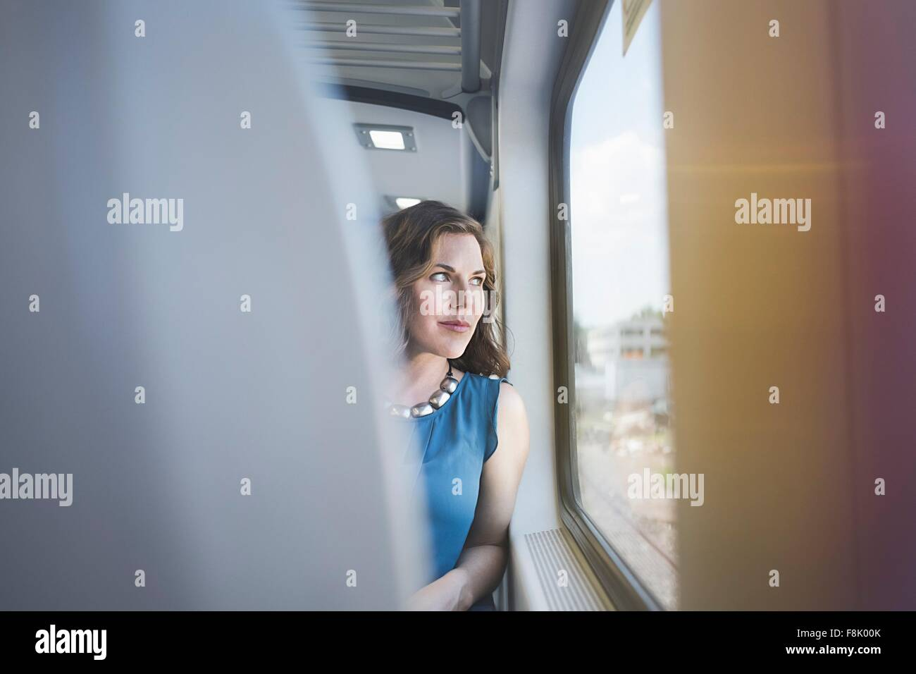 Mid adult woman on train, looking out of window - Stock Image