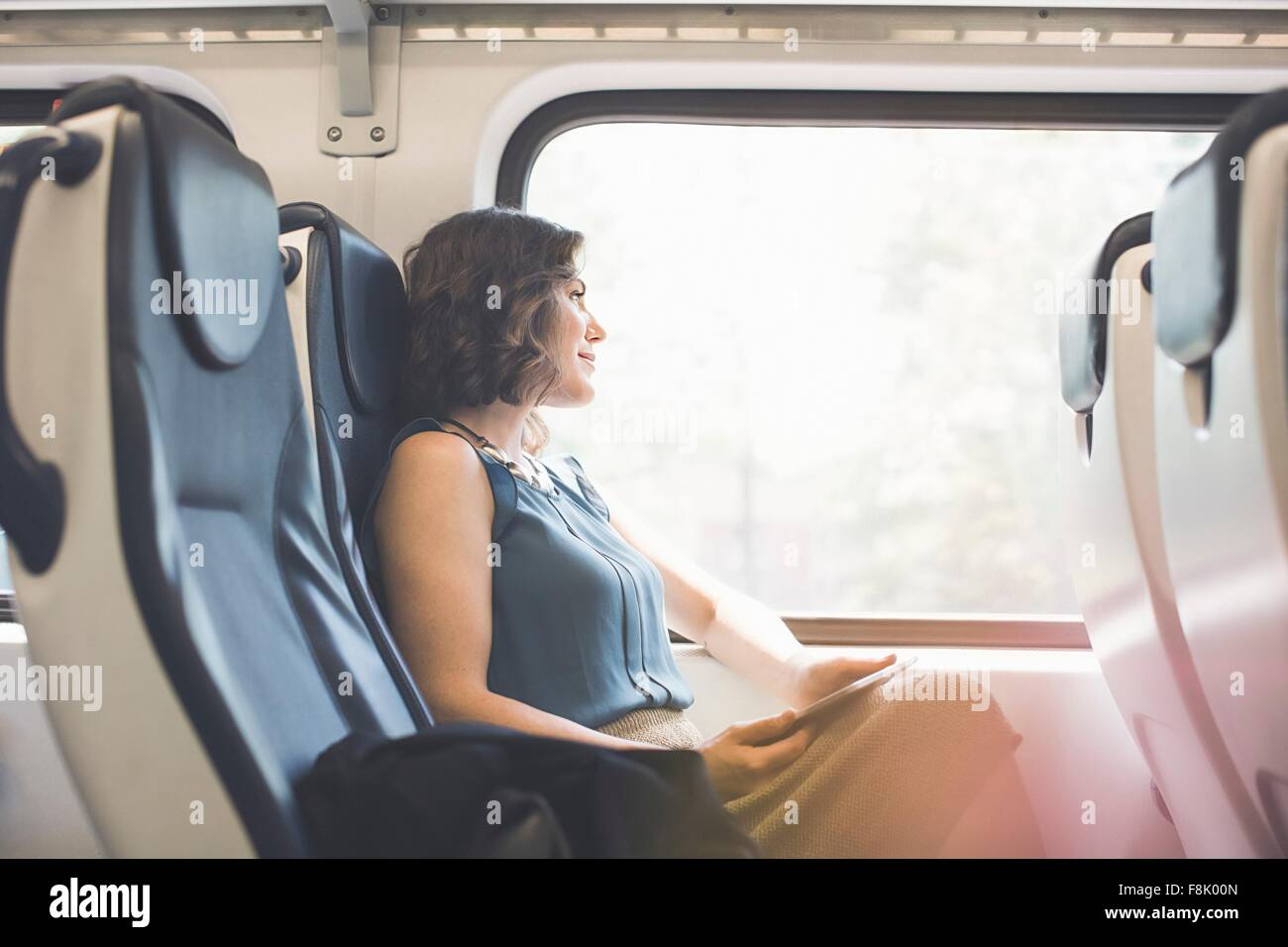 Mid adult woman on train, holding digital tablet, looking out of window - Stock Image