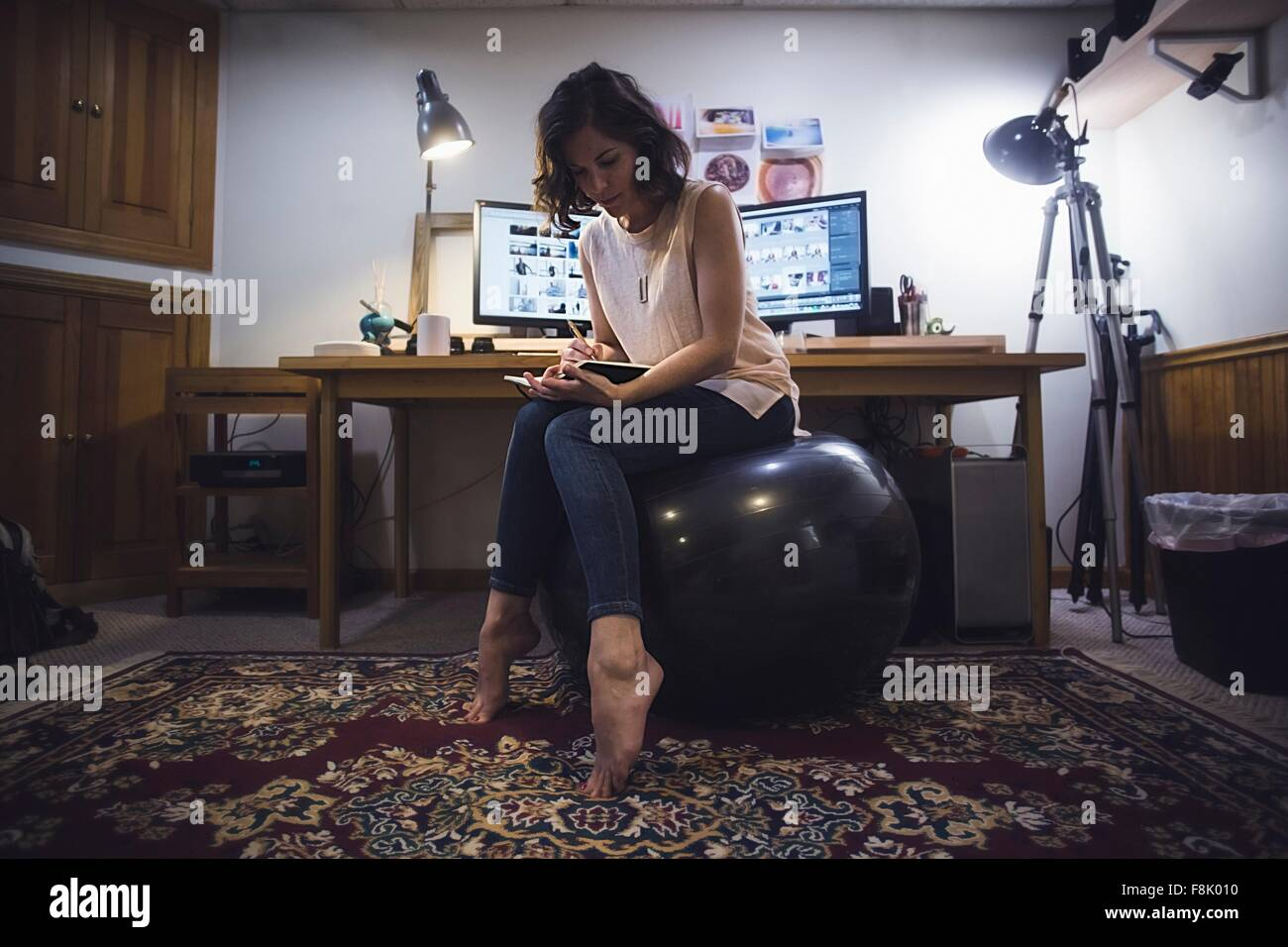Mid adult woman sitting on yoga ball, writing in diary - Stock Image
