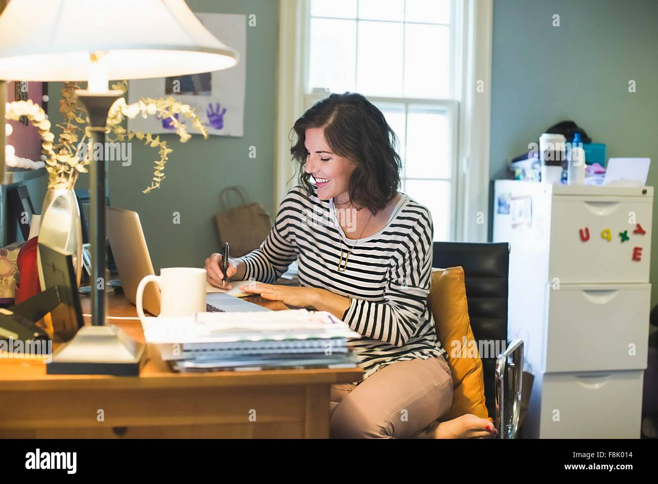 Mid adult woman at desk, laptop and coffee cup in front of her, writing in book - Stock Image