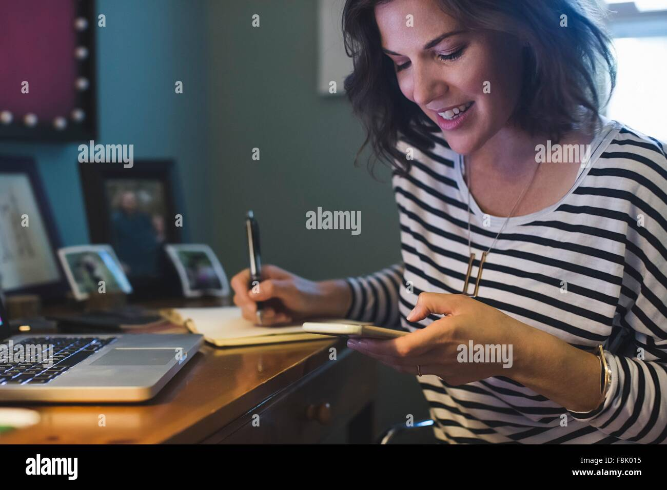 Mid adult woman at desk, holding smartphone, writing in book - Stock Image
