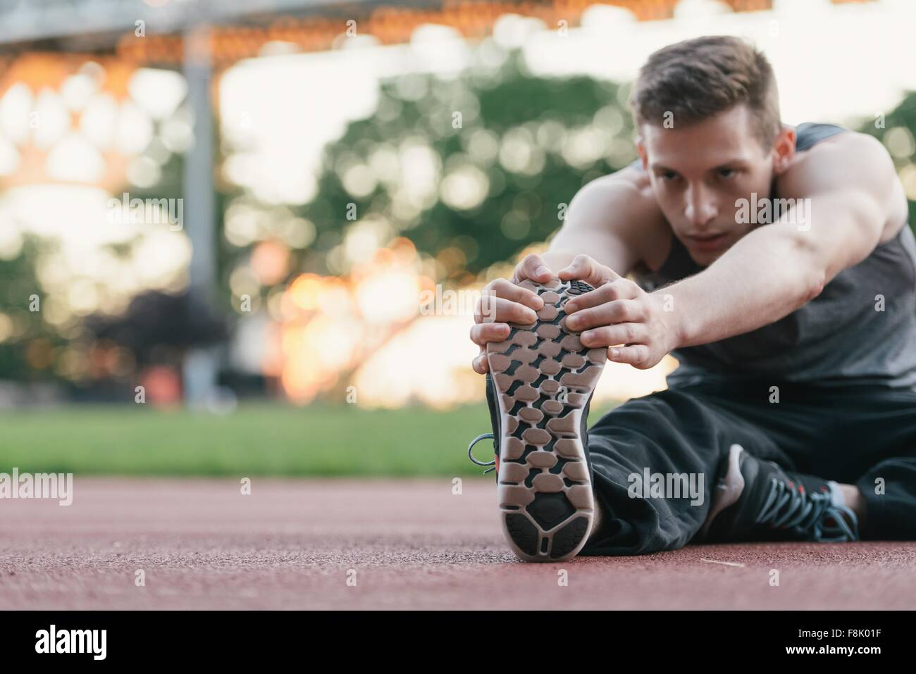 Young man on sports track, holding foot, stretching - Stock Image