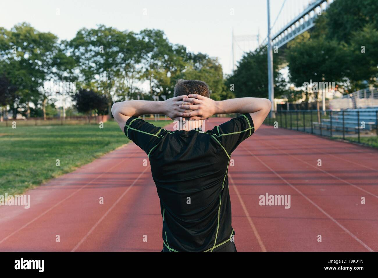 Young man on sports track, hands behind head, rear view - Stock Image