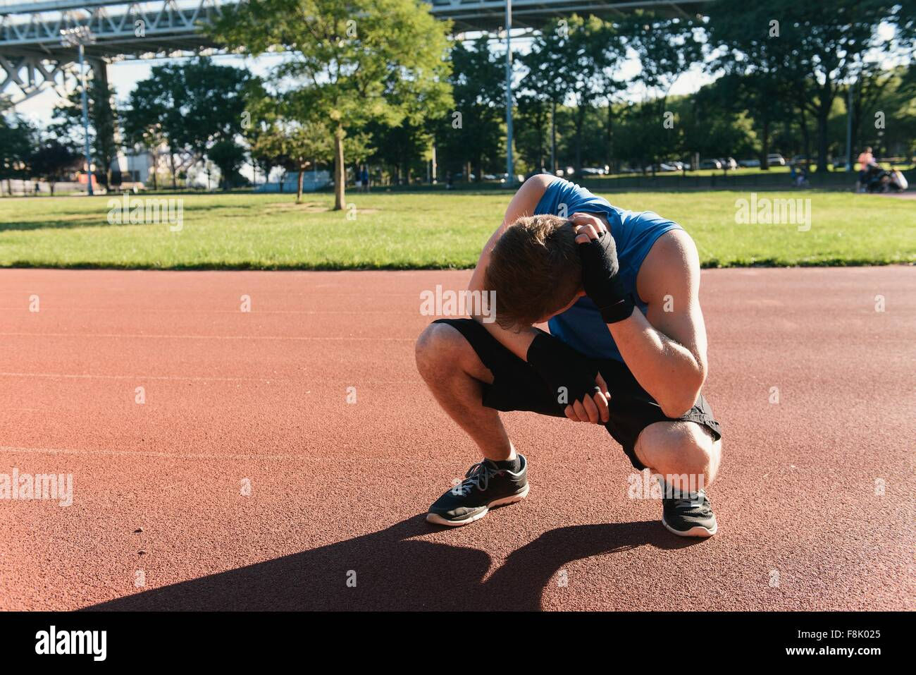 Young man outdoors, taking a break after exercise - Stock Image
