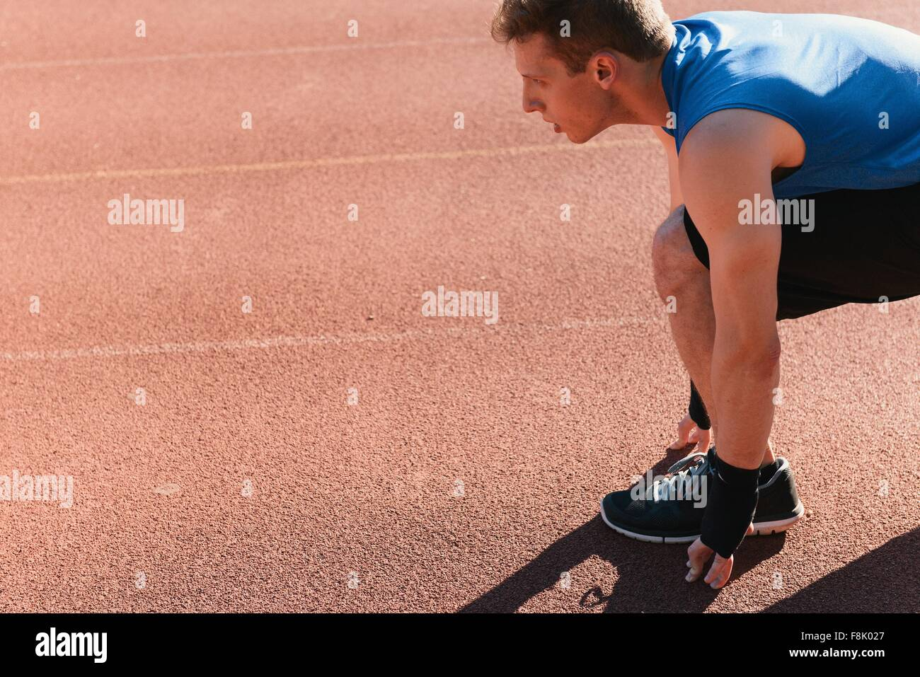 Young man in starting position on sports track - Stock Image