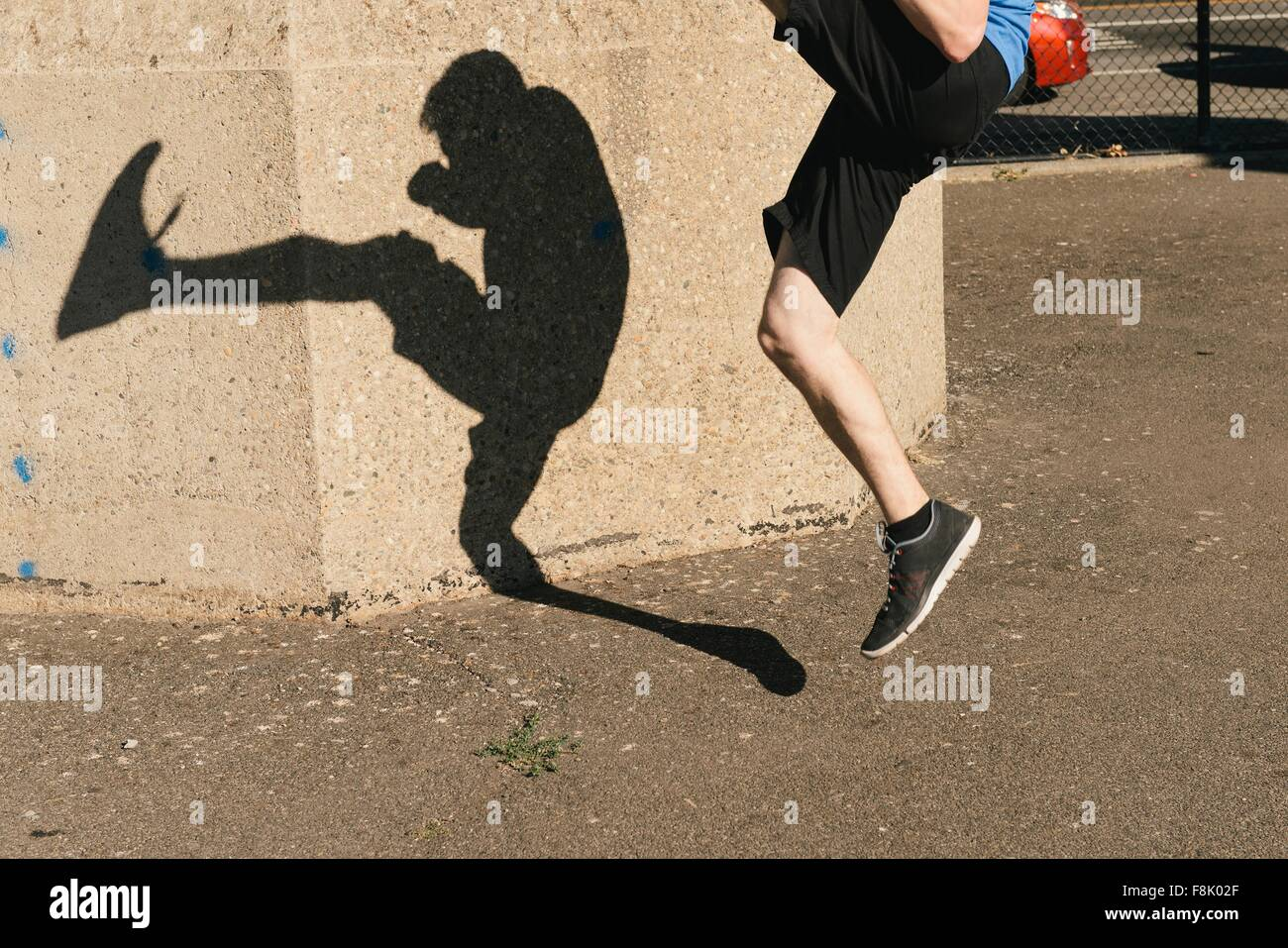 Young man shadow kickboxing, outdoors - Stock Image