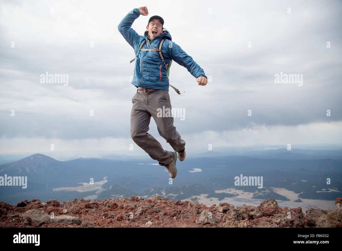 Young man jumping for joy at the summit of South Sister volcano, Bend, Oregon, USA - Stock Image