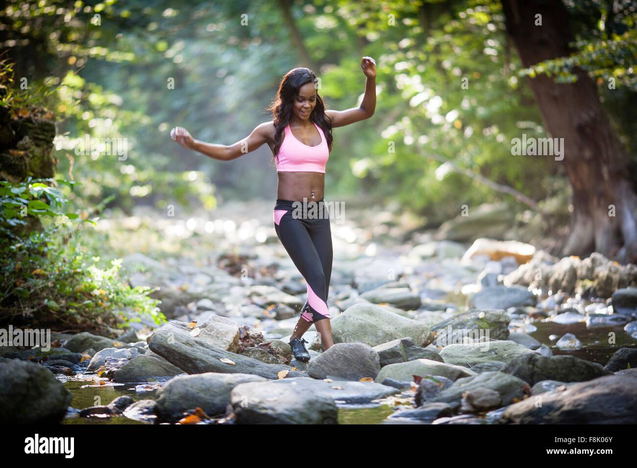 Young female hiker stepping over forest river rocks - Stock Image