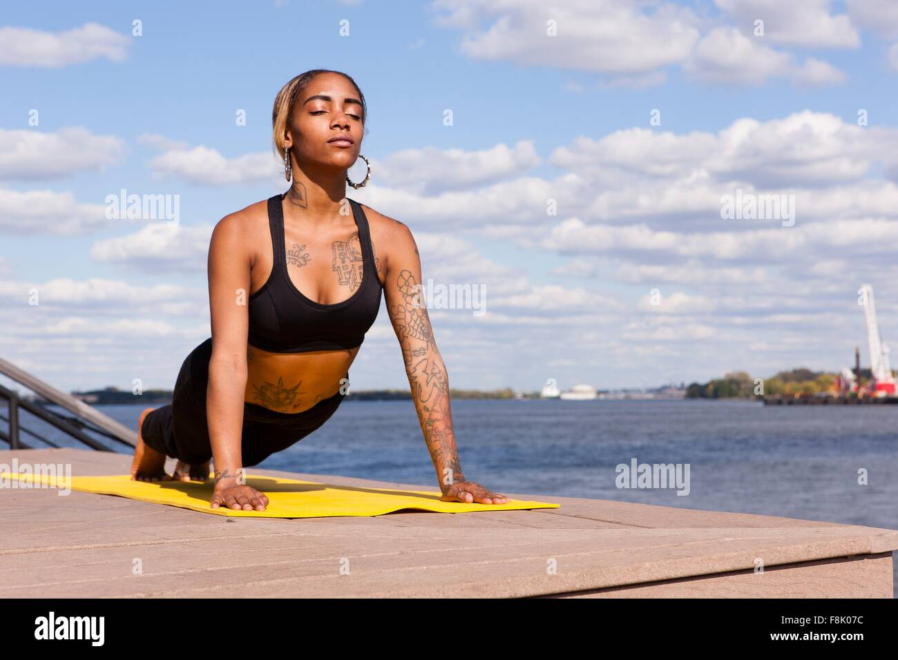 Young woman resting on hands by water in yoga position, eyes closed, Philadelphia, Pennsylvania, USA Stock Photo